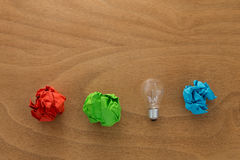 Great idea concept with crumpled colorful paper and light bulb. On wooden table royalty free stock photos