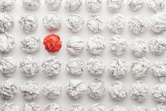 Great idea concept on the white office table. Overhead shot of crumpled paper in oder and red one standing out. great idea concept on the white office table Royalty Free Stock Image