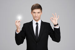 Great idea! Hansome young businessman holding a light bulb. Against gray background Royalty Free Stock Image