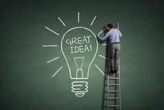 Great idea. Inspiration concept businessman standing on a ladder drawing a light bulb metaphor for great idea stock photo