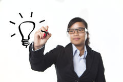 Great Idea. A woman drawing a light bulb in the air Royalty Free Stock Images