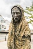 Great Irish Famine statue in Dublin, Ireland. Dublin, Ireland - August 7, 2017: Great Irish Famine bronze statue set on Custom House Quay along Liffey River in Stock Photography