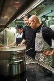 Great job. Cheerful professional chef looking how his two assistants are cooking in a restaurant kitchen. Preparing food royalty free stock photography