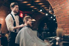 Great job! Hairstylist and a client in a barber shop. Red bearded young man got a stunning hairdo and his beard got royalty free stock photos