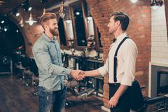 Great job! Happy satisfied client in a barber shop. Red bearded stock image