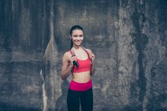 Great job! Happy young sport woman in stylish training outfit wi. Th jumping rope on her shoulders is smiling, standing outside on a concrete wall`s background royalty free stock images
