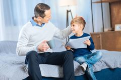 Loving father praising his son for nice picture. Great job. Loving young father patting his sons head, praising him for a beautifully drawn picture, while Royalty Free Stock Image
