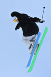 Great jump. Skier performs a high jump and turns to touch the back of his skis Royalty Free Stock Image