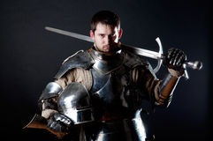 Great knight holding his sword and helmet. Powerful heavy fighter with sword and helmet Royalty Free Stock Photo