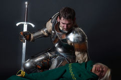 Great knight looking at dead  body. Knight looking at dead assassin Royalty Free Stock Photos