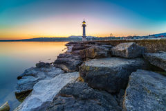 Great Lake Lighthouse Sunrise with Rocks. Geneva city, Switzerland Royalty Free Stock Images