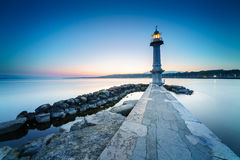 Great Lake Lighthouse Sunrise with Rocks. Geneva city, Switzerland Royalty Free Stock Photography