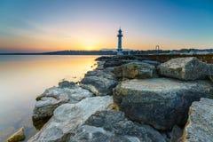 Great Lake Lighthouse Sunrise with Rocks Royalty Free Stock Photo