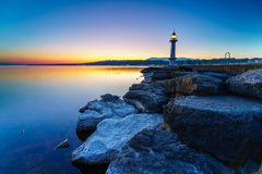 Great Lake Lighthouse Sunrise with Rocks. Geneva city, Switzerland Stock Photos