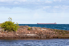 Great Lakes Freighter Passing Behind a Rocky Island Stock Image