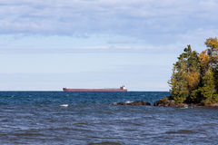 Great Lakes Freighter Passing Behind a Rocky Island Stock Photo