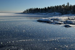 Great Lakes Frozen Shoreline Lake Superior. Frozen Lake shoreline on a clear Winter day, snow-covered rocky shoreline and shiny blue ice surface and with white Royalty Free Stock Photos