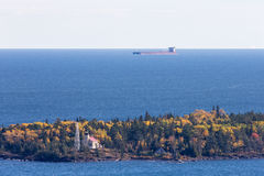 Great Lakes Oar Boat Passing Behind a Lighthouse Royalty Free Stock Images