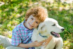 Great leisure with a pet. For one cute redhead boy with curly hair who looks right in the camera with the face full of joy. Little child embraces his dog royalty free stock photo