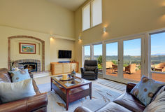 Great living room interior with high vaulted ceiling. Glass doors lead to the walkout deck. Northwest, USA Stock Photo