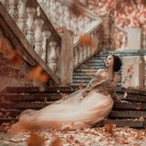 Great-looking charming dark-haired brunette girl sitting alone on the stone steps of an amazing royal castle, pretty. Magician in a long elegant golden dress stock images