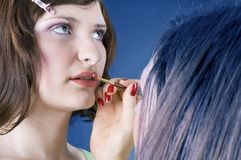 Great make-up. Young woman with her make-up artist applying lipstick Stock Photos