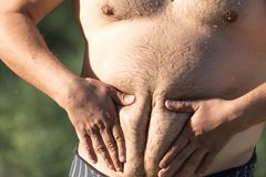 Great man`s stomach. In the park in nature Royalty Free Stock Photography