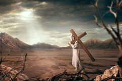 Great martyr with cross in desert, sun rays. The great martyr with cross in desert, cloudy sky with sun rays. Crucifixion of Jesus Christ, symbol of christian Stock Image