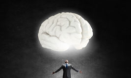 Great mental ability. Businessman with hands spread wide and human brain above his head Royalty Free Stock Image