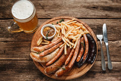 Great mix of sausages with beer on wood background. Traditional Oktoberfest menu. Mug of beer and various sausages served with sauce and french fries on wooden Royalty Free Stock Photos