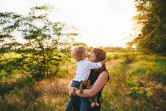 Great mother in black clothes is kissing her son on the wheat and wildflowers background. Family conception.  royalty free stock photos
