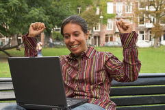 Great news. Excited girl sitting on a park bench with laptop computer Royalty Free Stock Images