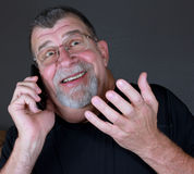 Great News. An adult man with a big smile talks on his mobile phone Stock Photography