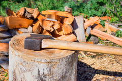 Great old hatchet against the pile of firewood. Concept - firewood for heating, the journey into the wild. Background blur Stock Photography