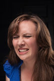 Great pain. Portrait of loud girl. Girl screams in pain. Close-up face. Dark background Stock Photo