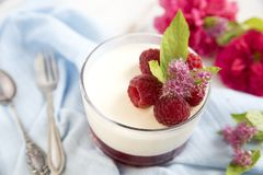 Great panacotta dessert with raspberries, on a blue background and vintage spoon and fork. royalty free stock photos