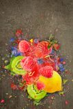 Artfully and lovingly designed fruit explosion with raspberries, blackberries, strawberries, kiwis, lemon and water. Great photo montage with explanting berries stock photo