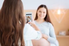 Small cute girl helps to collect memory. Great picture. Brunette little girl standing with her back and taking photo while her gorgeous pregnant mother Stock Photo