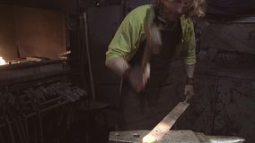 A great plan of a blacksmith at work. Blacksmith pulls out a red-hot workpiece and begins to forge it on the anvil. Very cinematic
