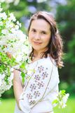 Beauty woman with fancy dress in spring landscape. Great portrait of amazing brunette woman in fancy dress among blossom trees. Sensual and gorgeous woman in Stock Photography