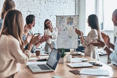 Great presentation. Group of business people clapping and smiling while standing in the board room stock photo