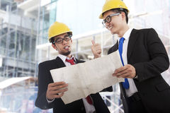 Great project. Portrait of two young builders standing at building site and discussing new project together Stock Photos
