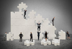 Great puzzle. Business team working to build a puzzle Stock Photo