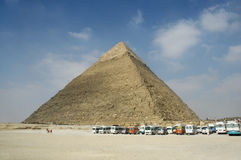 Great Pyramid of Giza. Scenic view of the Great Pyramid of Giza with row of buses or vans, blue sky and cloudscape background, El Giza, Egypt Stock Photos
