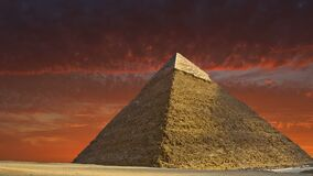 Great Pyramid of Giza, Egypt Travel, Sunrise, Sunset. The Great Pyramid of Giza in Cairo, Egypt. A sunrise or sunset casts a red glow in the background of the stock video