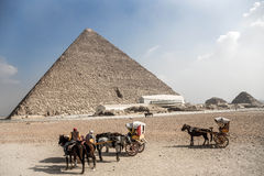 Great Pyramid of Giza. Porters wait near The Great Pyramid of Giza (also known as the Pyramid of Khufu or the Pyramid of Cheops) is the oldest and largest of the Royalty Free Stock Image