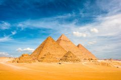 The Great Pyramids in Giza. The Great Pyramids of Giza with blue sky and clouds, photo taken on a sunny day in december in egypt royalty free stock photo
