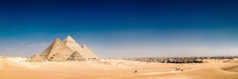 The great pyramids of Giza, Egypt. Panorama of the area with the great pyramids of Giza, Egypt, with the skyline of Cairo in the background stock images