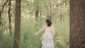 Great queen in a transparent white luxurious light vintage summer dress with flower patterns inspects her possessions. Walking slowly through the woods, moving stock footage
