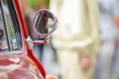 Great red oldtimer vintage car detail: mirror with blur copyspace. Background for your text Royalty Free Stock Photos